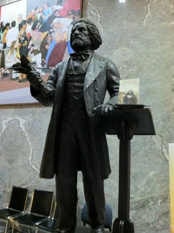Before the Frederick Douglass statue at One Judiciary Square moves to the US Capitol he takes time to read a new book about his life and times in Anacostia. Photo_ John Muller