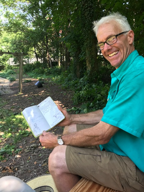 Ron Ammon sitting on new bench w Journal of drawing of him - FDNHS - 7.1.2018